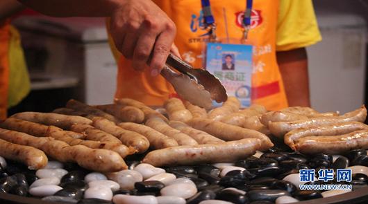 两岸各大夜市的招牌美食集聚特色庙会,图为鹅卵石上的香肠,香气四溢。新华网 刘默……