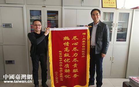 凯普松电子科技(包头)有限公司总经理林鸿儒(左,台湾籍)向自治区台办赠送锦旗