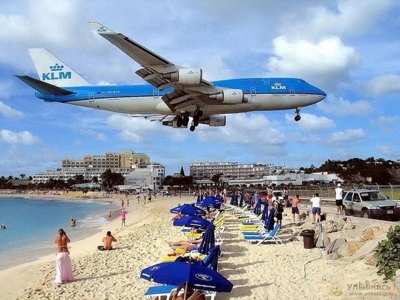 一架荷兰皇家航空的飞机低空飞过Maho海滩,游客纷纷拍照。   据weirdexistence.com网站报道,荷属安地列斯群岛的圣马丁岛上的Maho度假海滩被认为是世界上最诡异的海滩,它面对着荷兰,但隔着一条马路就是朱莉安娜公主国际机场。度假者常常可以看到头顶上驶过的大飞机,还常被飞机驶过带来的狂风吹得不得不抓住栏杆。   但是从乘机者的角度看就不一样了,如果从飞机上跳下就可以直接跳进海里,开始自己的度假。   维基百科上是这么介绍这个海滩的:   Maho海滩位于荷属安帝列斯群岛圣马丁岛上,面对荷