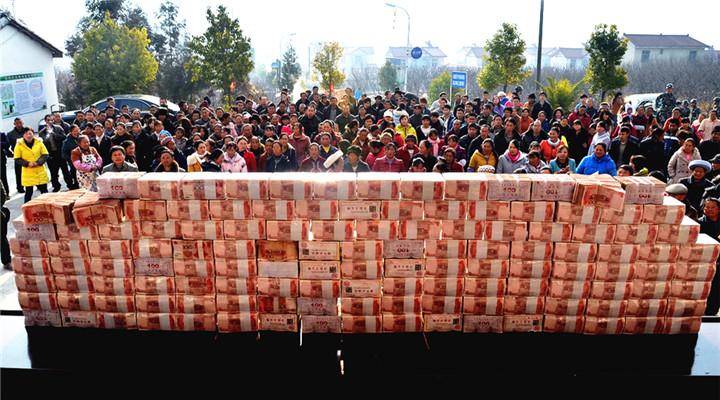 人民币墙堆起 村里人走上致富路