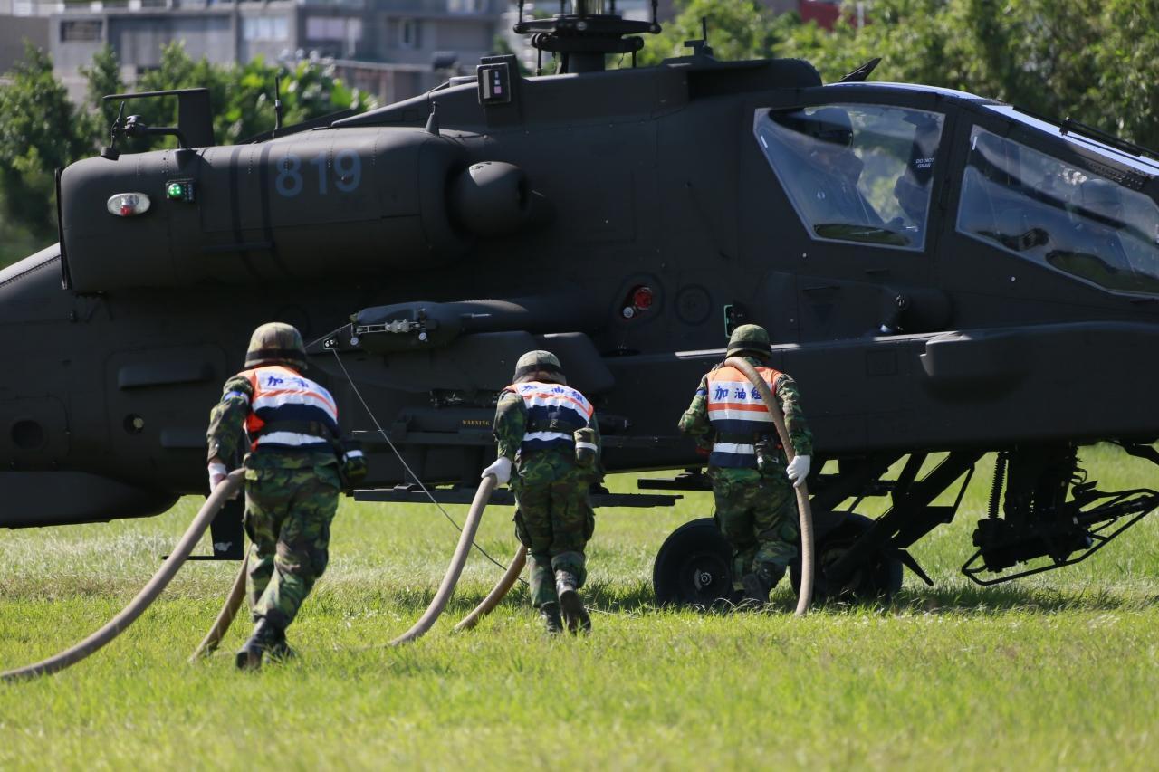 """台军陆航AH-64E阿帕契直升机8日参与""""汉光31号""""演习实兵演练,执行整补作业的官兵完成装弹"""