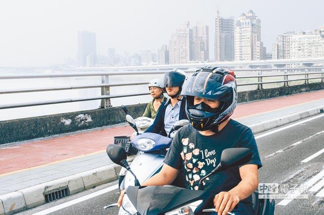 图为一位民众骑经台北市桥梁,天空雾茫茫。(《中国时报》 郭吉铨摄)