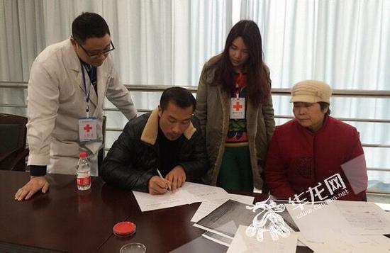 小月父親鄧師傅在登記表上簽字。 市紅十字會供圖 華龍網發